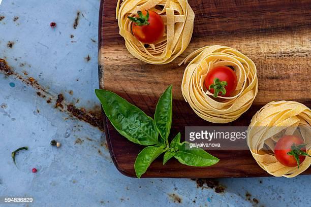 Fettuccini, tomatoes and basil on a chopping board