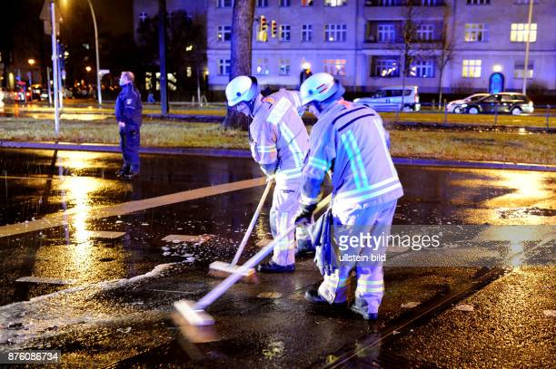 Feuerwehrmänner fegen nach einem Verkehrsunfall Fahrzeugteile von einer Fahrbahn in BerlinPrenzlauer Berg