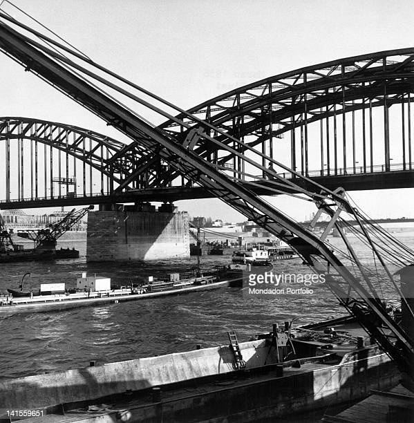 Few boats sailing the river Rhine passing under a huge iron bridge Cologne March 1956