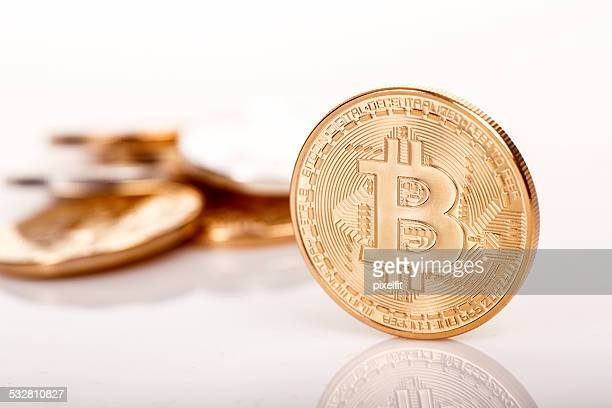 Few golden bitcoins on white background.