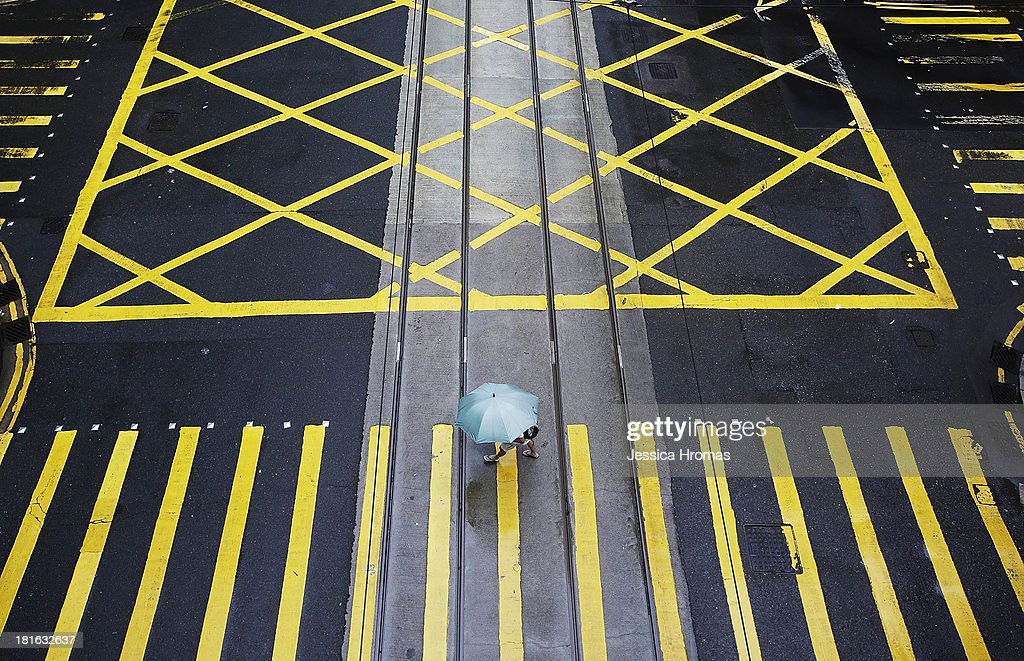 A few pedestrians walk along a quiet Des Voeux Road in Hong Kong's CBD on September 23, 2013. A category typhoon eight warning was in place till 9:30am as Typhoon Usagi swept by Hong Kong. Most businesses are closed if a category eight typhoon is in place.