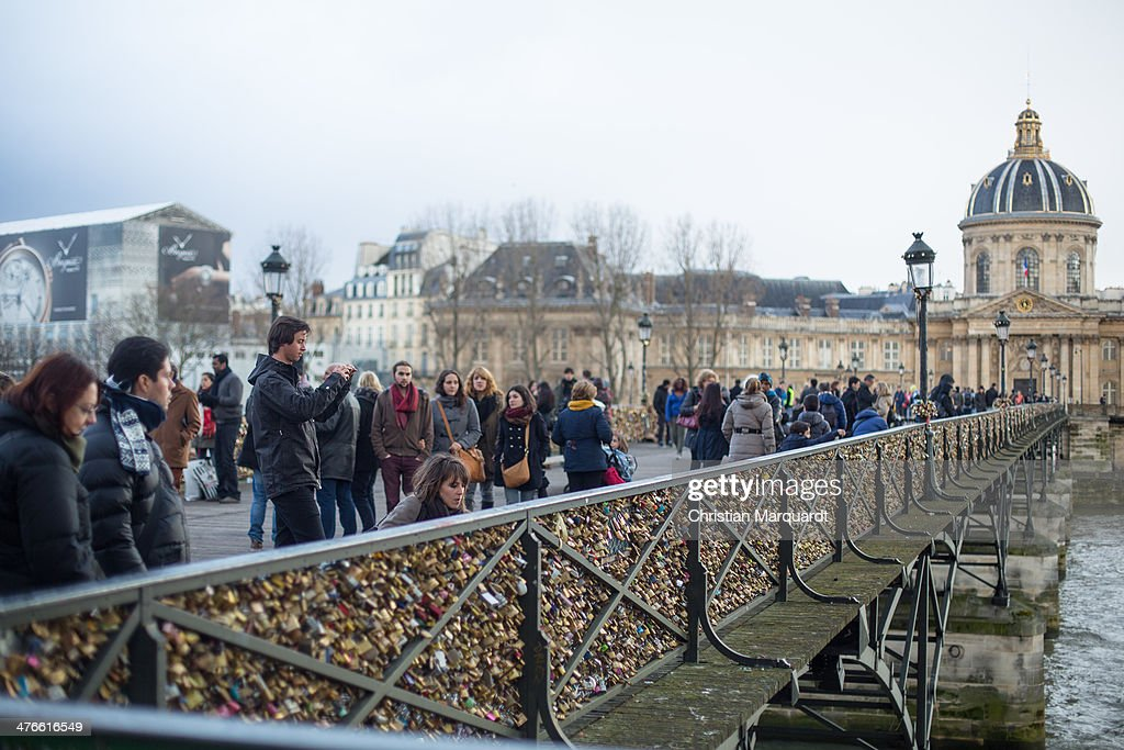 Few people cross the Bridge of Arts (Pont des Arts) with the libary of Mazarine at the horizon during a rainy day on February 28, 2014 in Paris, France. The libary of Mazarine is Couples attach locks as a sign of their love to the railing of the bridge.