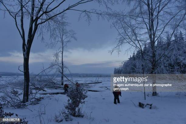 A few people in middle snowy nature under dim light