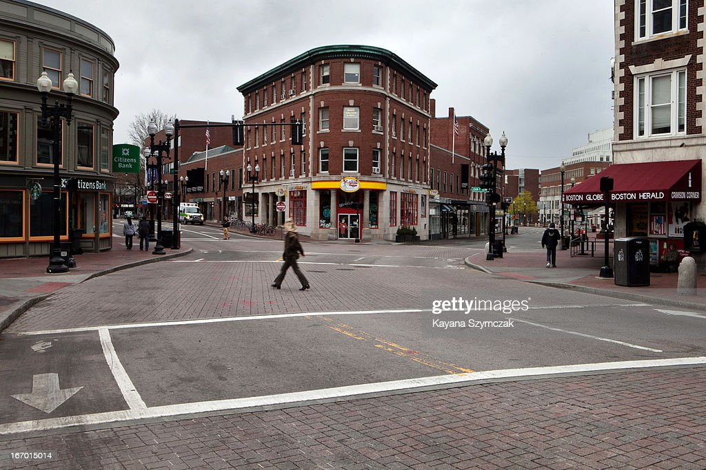 A few people walk through an otherwisedeserted Harvard Square on April 19 2013 in Cambridge Massachusetts After a car chase and shoot out with police...