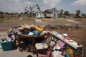 A few possessions stacked at the corner of the foundation is all that remains of a home destroyed by the May 22 tornado July 29 2011 in Joplin...