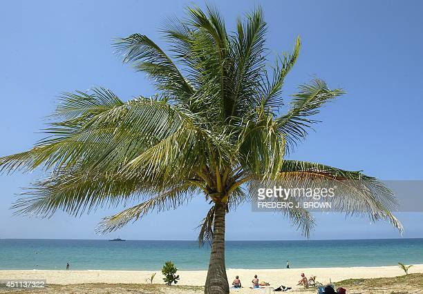 A few tourists sit under the sun on a deserted Karon Beach in Phuket southern Thailand 29 January 2005 as ministerial meetings on regional...