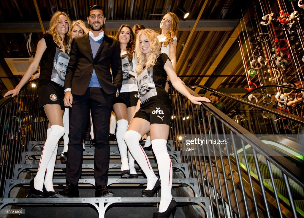Feyenoord Rotterdam player Graziano Pelle (C) poses after receiving a t-shirt with his portrait on it from a Dutch stylist during the presentation of the t-shirt in Rotterdam, The Netherlands, on November 27, 2013. Fashion label Eleven Paris previously launched the t-shirt with Lady Gaga, Kate Moss and Pharrell Williams on it.