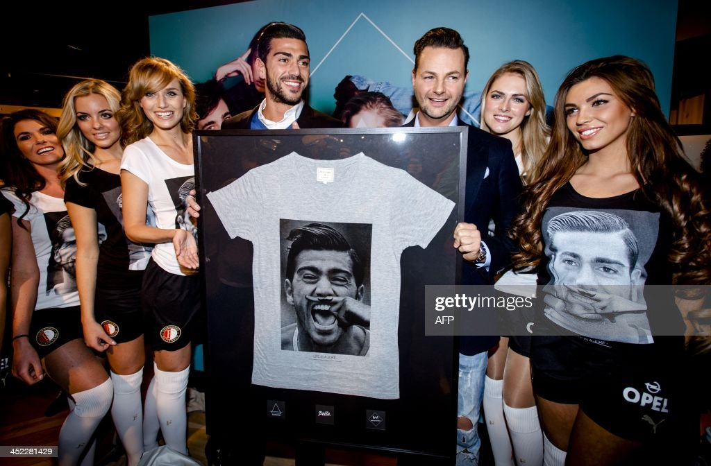 Feyenoord Rotterdam player Graziano Pelle (L) receives a t-shirt with his portrait on it from Dutch stylist Fred van Leer (R) during the presentation of the t-shirt in Rotterdam, The Netherlands, on November 27, 2013. Fashion label Eleven Paris previously launched the t-shirt with Lady Gaga, Kate Moss and Pharrell Williams on it.