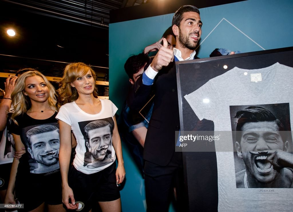 Feyenoord Rotterdam player Graziano Pelle receives a t-shirt with his portrait on it from a Dutch stylist during the presentation of the t-shirt in Rotterdam, The Netherlands, on November 27, 2013. Fashion label Eleven Paris previously launched the t-shirt with Lady Gaga, Kate Moss and Pharrell Williams on it.