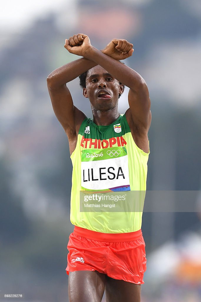 Feyisa Lilesa of Ethiopia celebrates as he crosses the line to win silver during the Men's Marathon on Day 16 of the Rio 2016 Olympic Games at Sambodromo on August 21, 2016 in Rio de Janeiro, Brazil.