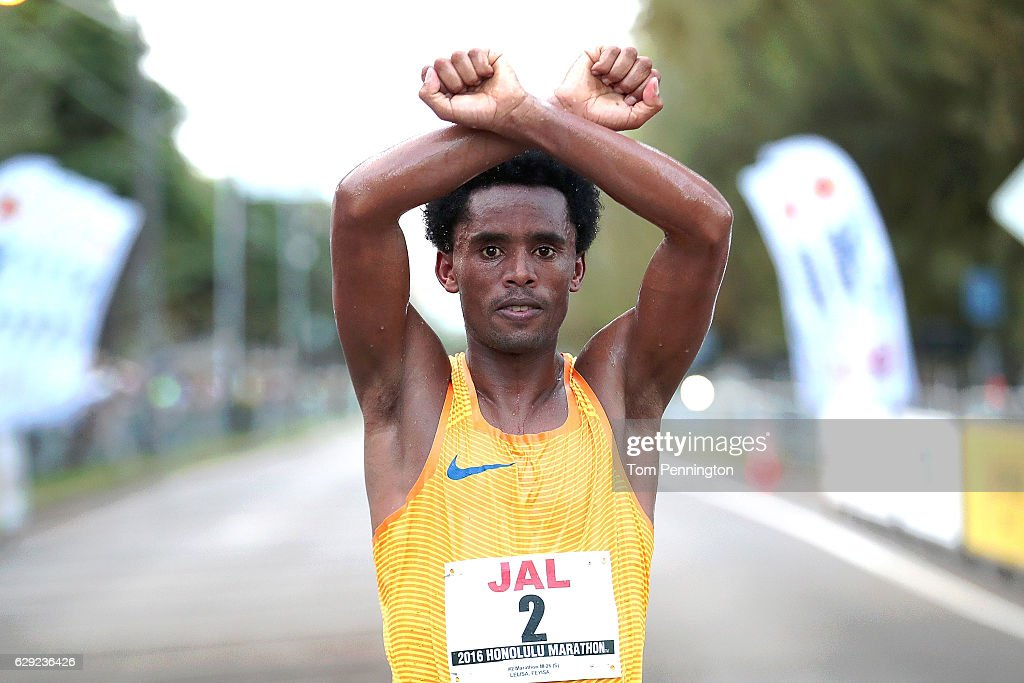 Feyisa Lilesa of Ethiopia poses for a photograph after crossing the finish line during the Honolulu Marathon 2016 on December 11, 2016 in Honolulu, Hawaii.