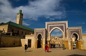 Fez medina gate with people and green mosque