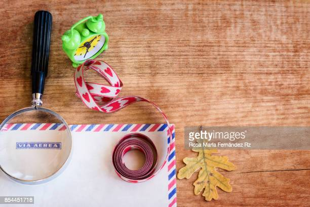 ffice supplies. Magnifying glass, envelope, oak leaf, alarm clock and ribbon on wooden table background.  High angle view and copy space.