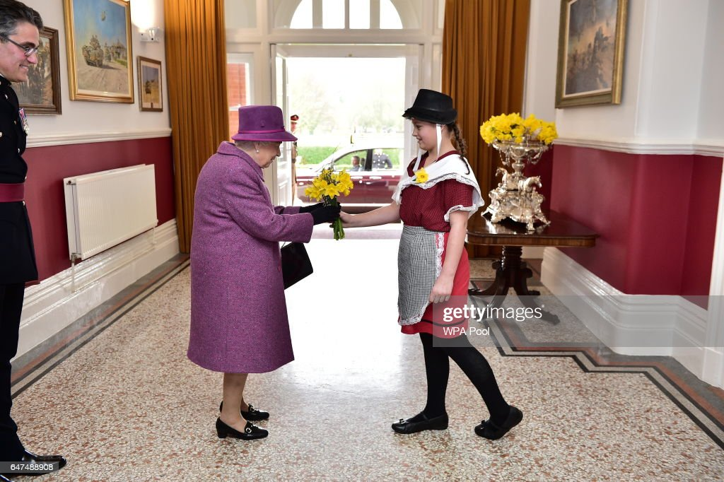 Ffion Williams, 10, presents a bunch of daffodils to Queen Elizabeth II as she visitsThe Royal Welsh Regimental Family to mark St David's Day at Lucknow Barracks on March 3, 2017 in Tidworth, England.