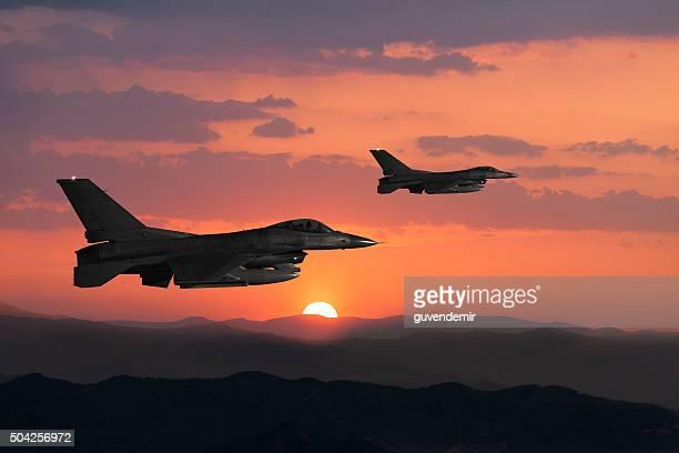 F - 16 Falcons contre en vol au coucher du soleil