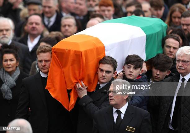 Fiachra McGuinness and Emmett McGuinness carry the coffin of the late Martin McGuinness as it arrives at St Columba's Church on March 23 2017 in...