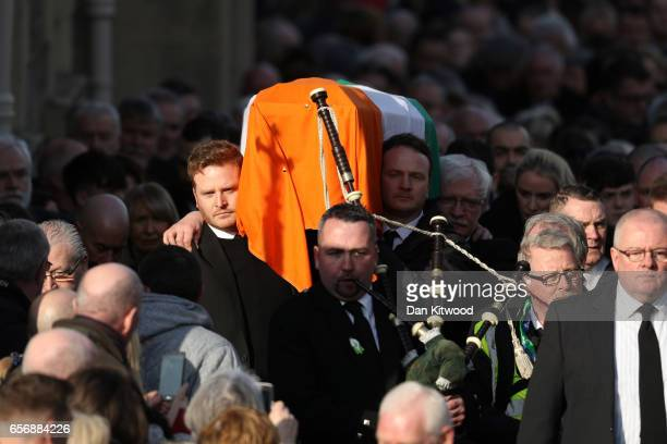 Fiachra McGuinness and Emmett McGuinness carry the coffin of the late Martin McGuinness after the funeral service at St Columba's Church on March 23...