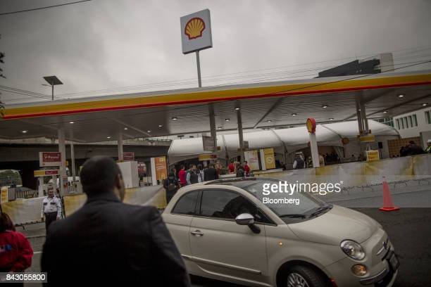 A Fiat Chrysler Automobiles NV 500 subcompact vehicle drives past as attendees celebrate the opening ceremony of the first Royal Dutch Shell PLC...