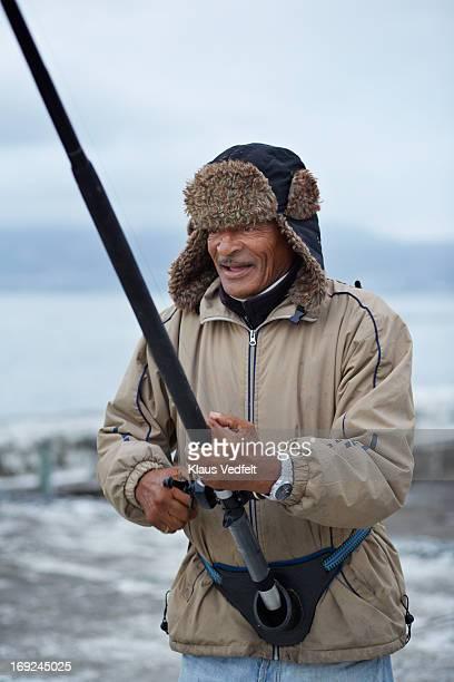 Ficherman wheeling in fish with rod