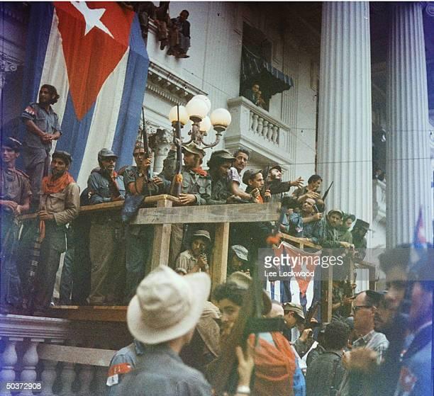 Fidel Castro in Santa Clara orating from makeshift balcony draped w Cuban flags in Santa Clara en route to victorious entry into Havana