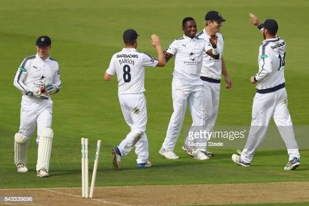 Fidel Edwards of Hampshire celebrates with Liam Dawson and James Vince after taking the wicket of Ryan Patel of Surrey during day two of the...
