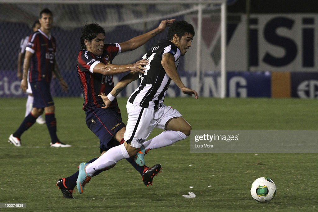 Fidencio Oviedo (R) of Cerro Porteño and Ariel Nuñez (L) of Libertad fight for the ball during the match between Libertad and Cerro Porteño for the Aperture APF, at Defensores del Chaco on March 03, 2013 in Asuncion, Paraguay.