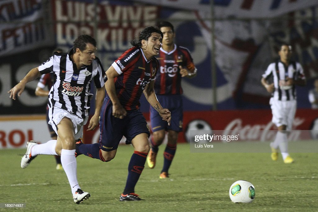 Fidencio Oviedo (R) of Cerro Porteño and Nelson Romero (L) of Libertad fight for the ball during the match between Libertad and Cerro Porteño for the Aperture APF, at Defensores del Chaco on March 03, 2013 in Asuncion, Paraguay.