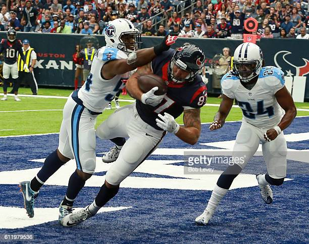 J Fiedorowicz of the Houston Texans catches a pass for a touchdown with Avery Williamson and Daimion Stafford of the Tennessee Titansof the Tennessee...