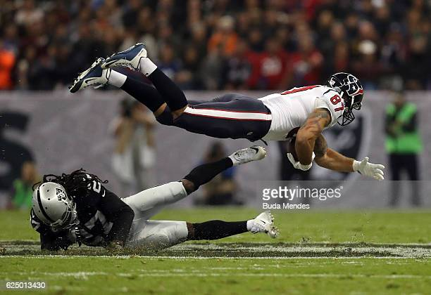 J Fiedorowicz of the Houston Texans is tackled by Reggie Nelson of the Oakland Raiders in their game at Estadio Azteca on November 21 2016 in Mexico...