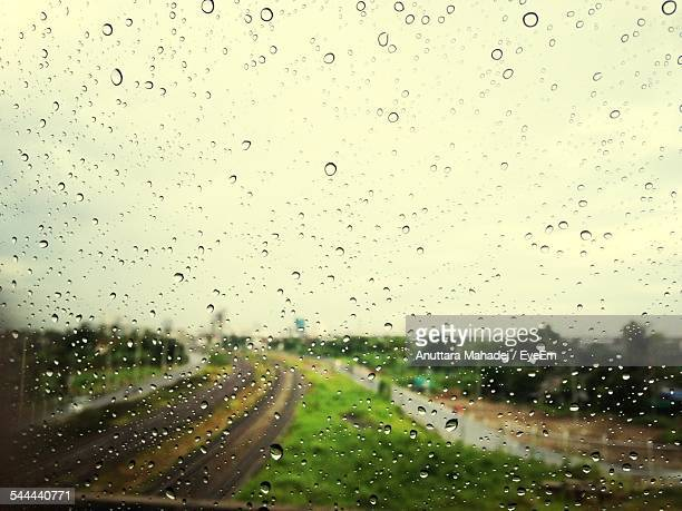 Field And Road Seen Through Wet Glass Window