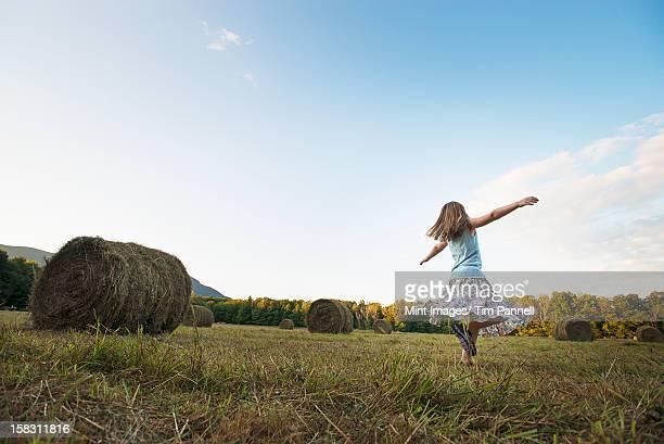 Ein Feld voller Hoher runder hay bales und ein Junge
