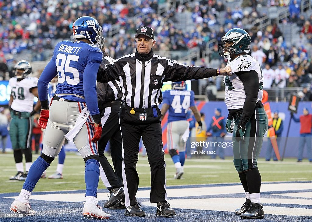 Field judge Gary Cavaletto seperates Martellus Bennett #85 of the New York Giants and Brandon Graham #54 of the Philadelphia Eagles after a play at MetLife Stadium on December 30, 2012 in East Rutherford, New Jersey. The Giants defeated the Eagles 42-7.
