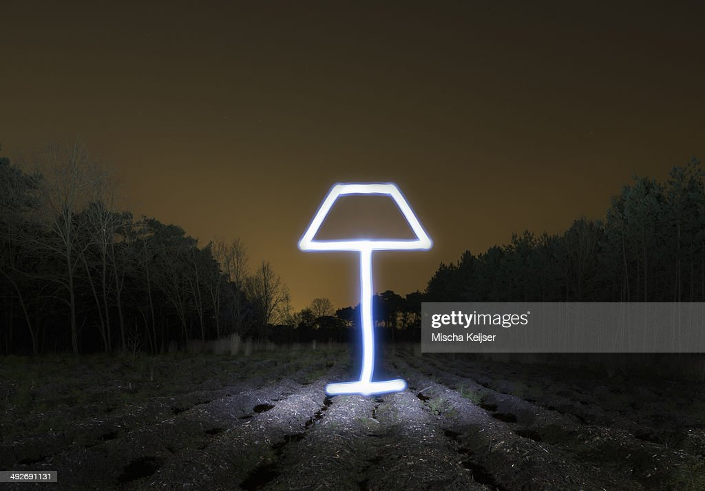 Field landscape at night with light painted drawing of lamp