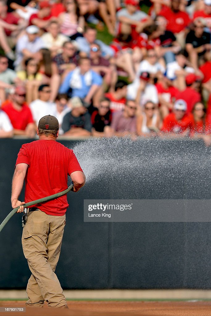 A field maintenance worker sprays water onto the field prior to a game between the North Carolina Tar Heels and the North Carolina State Wolfpack at Doak Field on April 26, 2013 in Raleigh, North Carolina. North Carolina defeated NC State 7-1.