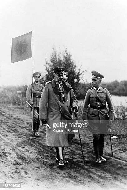 Field marshal and president of the German Reich Paul von Hindenburg followed by a soldier holding a banner during the Reichswehr maneuvers in the...