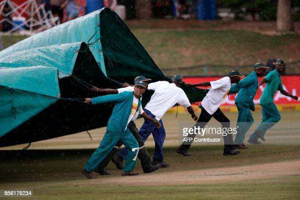 Field marshals and workers run to cover the pitch as rain starts during the fourth day of the first Test cricket match between South Africa and...