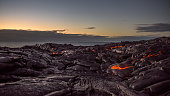 Walking on a field of lava on the Pacific coast near Kalapana on the Big Island of Hawaii at dawn.