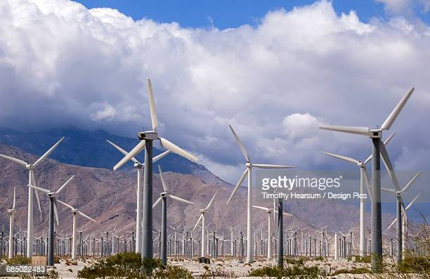 A field of wind generators with mountains and clouds in the background, a common sight in California