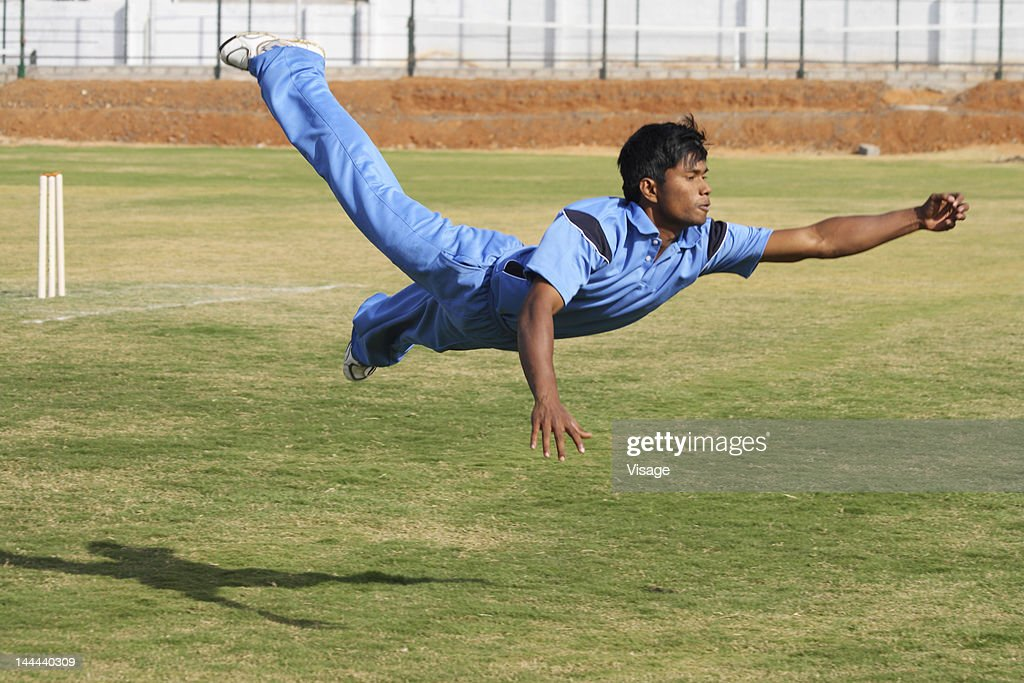A fielder attempting to catch the ball : Stock Photo