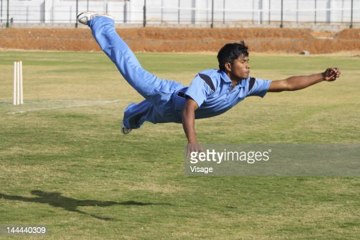 A fielder attempting to catch the ball : Stock-Foto