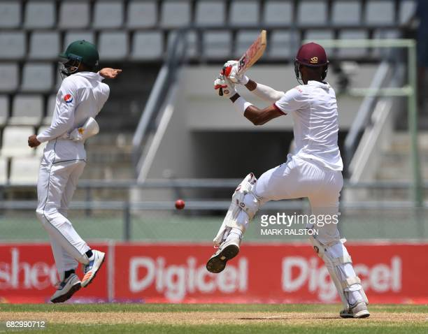 Fielder Babar Azam of Pakistan avoids a cover shot from West Indies batsman Roston Chase on the fifth day of play of the final test match at the...