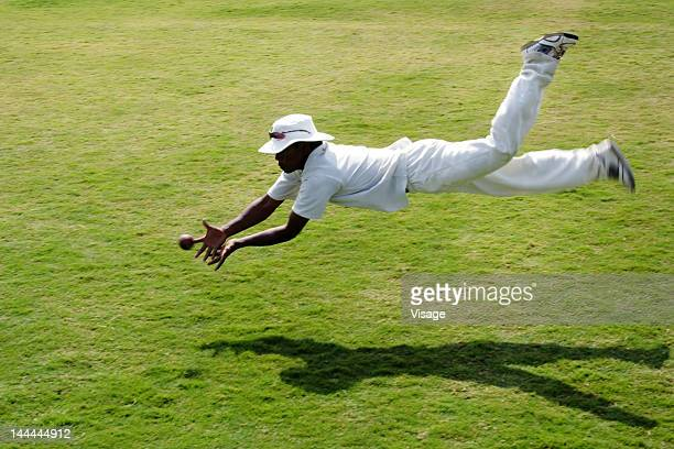 A fielder diving to take a catch