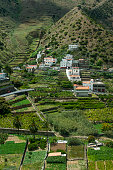 Fields and houses on the steep hillside along the coast near Vallehermoso on the island of La Gomera which is one of the Canary Islands Spain located...