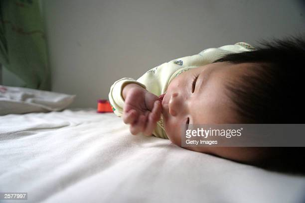 Fifteen month old QingQing lies on her bed before she leaves the Dongzhimen Hospital October 10 2003 in Beijing China QingQing was born with an extra...