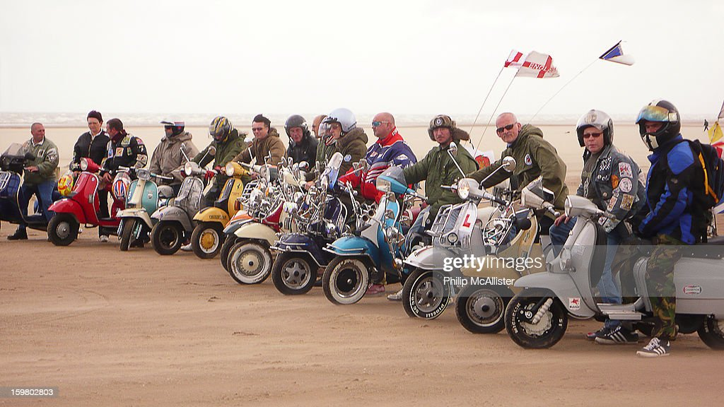 CONTENT] Fifteen scooterists line up on their scooters on a beach.They are in a line and it is windy.