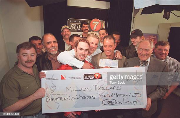 Fifteen workers at Johnson Matthey Ltd Brampton share aLotto Super 7 prize of $81 million They receive the big cheque from Ron Barbaro