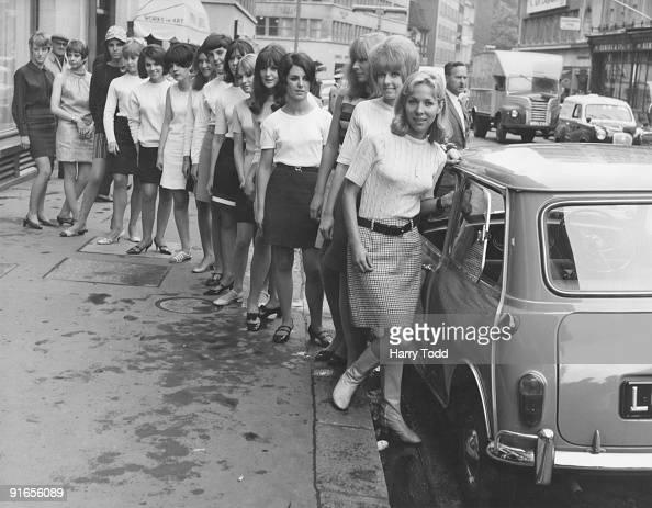 Fifteen young women in mini skirts wait to board a BMC Mini outside University Motors in Conduit Street London 21st July 1966 They are about to break...