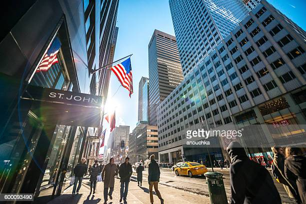 Fifth Avenue with luxury shops and people walking, NYC