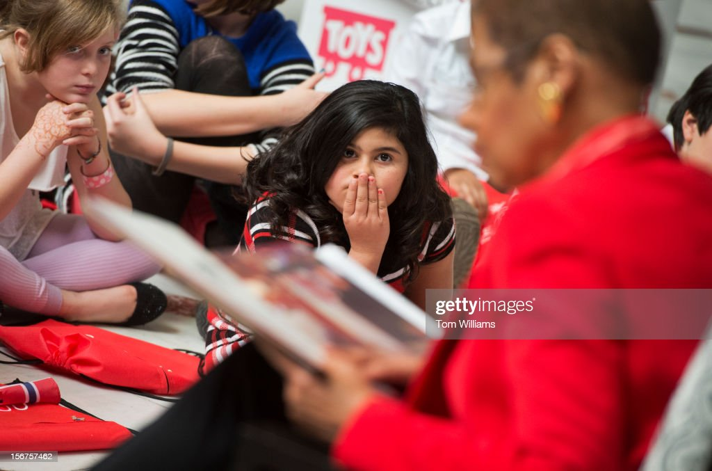 Fifth graders from Stoddert Elementary School including Valerie Lopez, center, listens to a Christmas story read by Del. Eleanor Holmes Norton, D-D.C., during the annual 'Toys for Tots' program held by the Marine Corps in Union Station.