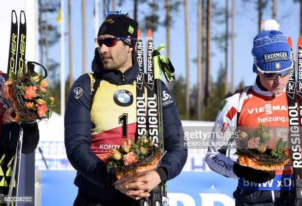Fifth placed Martin Fourcade of France and sixth placed Italy's Lukas Hofer receive flowers after the men's 125 km pursuit at the IBU Biathlon World...